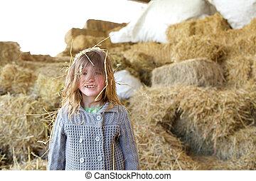 Una chica sonriendo en una granja con heno en el pelo