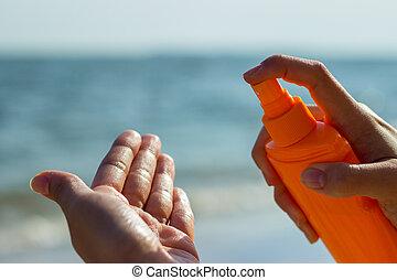 Una chica sosteniendo una botella de protector solar y aplicando protector solar en la palma de la mano en las vacaciones de la playa tropical, cerca de las manos. El concepto de la piel