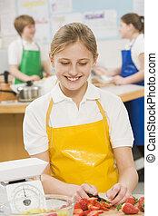 Una colegiala en una clase de cocina
