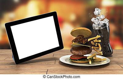 Una computadora de tablet con una pantalla en blanco en la mesa de madera con una hamburguesa y un vaso de cola con hielo libre para el texto 3D