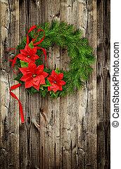 Una corona navideña de ramas de pino y flores de ponsettia