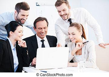 Una discusión de negocios. Un grupo de gente de negocios segura en ropa formal sentados juntos en la mesa y discutiendo algo mientras miran el portátil
