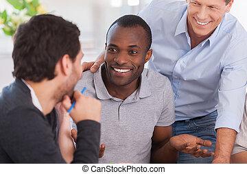 Una discusión de oficina. Un grupo de alegres empresarios sentados juntos en la mesa y discutiendo algo