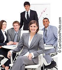 Una ejecutiva asertiva sentada frente a su equipo