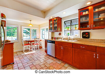 Una encantadora cocina de madera de cereza con piso de azulejo.