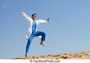 Una enfermera alegre saltando en la playa