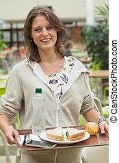 Una estudiante que lleva bandeja de comida en la cafetería
