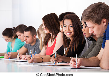 Una estudiante sentada con compañeros escribiendo en el escritorio