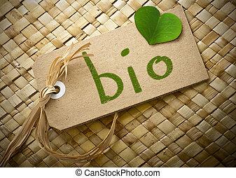 """Una etiqueta de cartón con la palabra """"biológico"""" y un pétalo de trébol verde"""