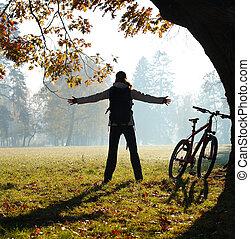 Una excitada ciclista parada en un parque con las manos extendidas abrazando la vitalidad. Afuera