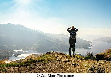 Una excursionista en la cima de la montaña disfrutando de la vista del valle, Ben a'an, Loch Katrina, Highlands, Escocia, Reino Unido