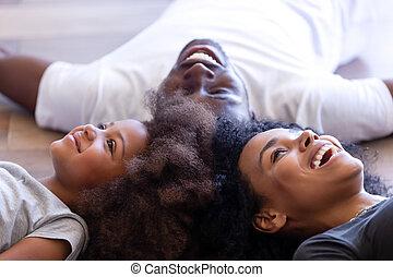 Una familia africana con una hija acostada en el suelo
