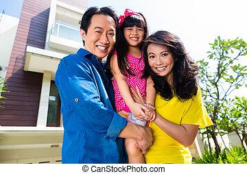 Una familia asiática con un niño delante de casa