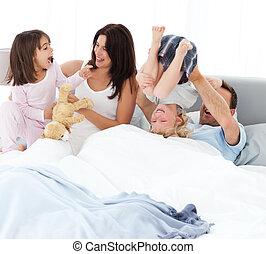 Una familia feliz jugando en la cama
