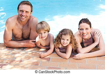 Una familia feliz junto a la piscina