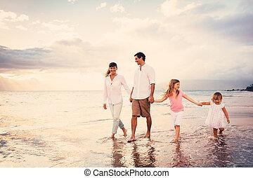 Una familia feliz se divierte caminando por la playa al atardecer