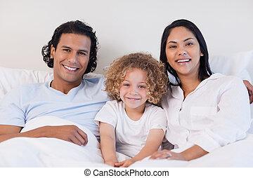 Una familia feliz sentada en la cama