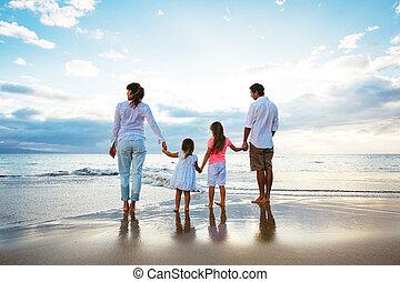 Una familia feliz viendo el atardecer en la playa