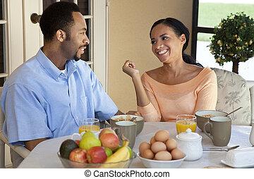 Una feliz pareja afroamericana de 30 años, sentada afuera, desayunando saludable