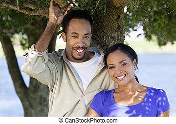 Una feliz pareja afroamericana junto bajo un árbol
