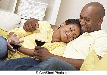 Una feliz pareja americana y una mujer bebiendo vino