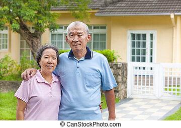 Una feliz pareja asiática delante de una casa