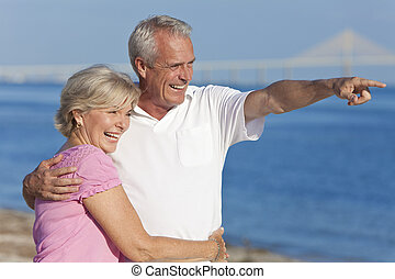 Una feliz pareja de ancianos caminando apuntando a la playa