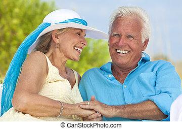 Una feliz pareja de ancianos de la mano riéndose de la playa