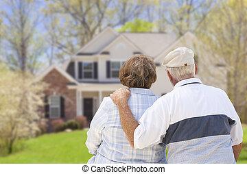 Una feliz pareja de ancianos mirando al frente de la casa