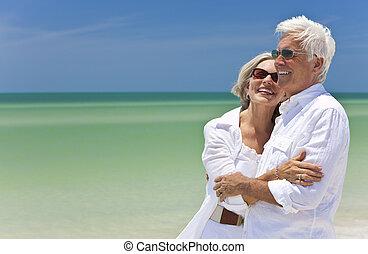 Una feliz pareja de ancianos mirando al mar en una playa tropical