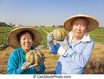 Una feliz pareja de ancianos parada frente a la granja