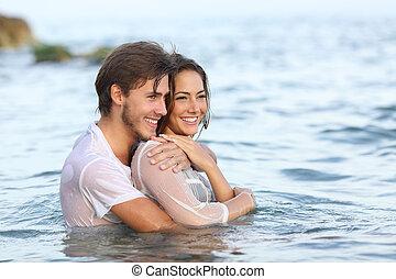 Una feliz pareja enamorada abrazando y bañándose en la playa