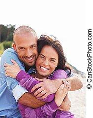 Una feliz pareja sonriente de mediana edad en una playa