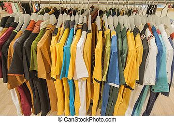 Una fila de camisetas colgando de una baranda