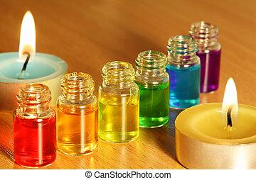 Una fila de seis botellas con aceites de colores y dos velas sobre la mesa