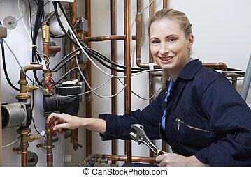 Una fontanero trabajando en una caldera de calefacción central