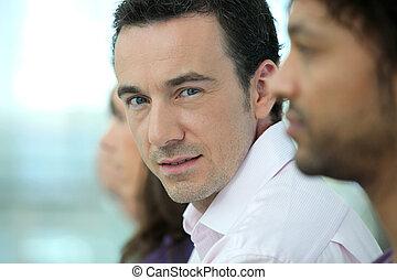 Una foto de un hombre guapo con colegas en una línea
