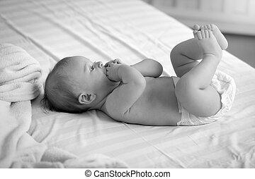 Una foto en blanco y negro de un lindo bebé en pañales acostado en la cama