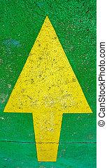 Una gran flecha amarilla apuntando con un fondo verde