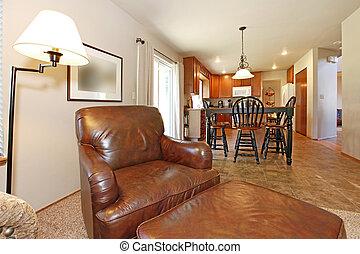 Una gran silla de cuero con vista a la cocina