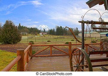 Una granja de caballos con vallas y una montaña Rainier
