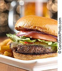 Una hamburguesa con queso con jarra de cerveza en el fondo