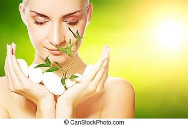 Una hermosa joven sosteniendo una planta creciendo a través de las piedras