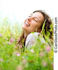 Una hermosa joven yaciendo en el prado de las flores. Disfruta de la naturaleza
