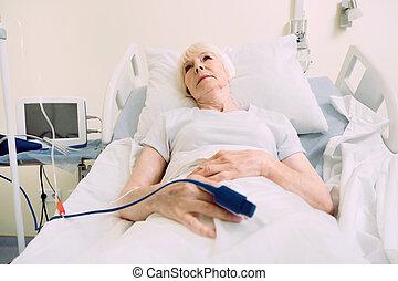 Una hermosa mujer jubilada en la cama con oxígeno