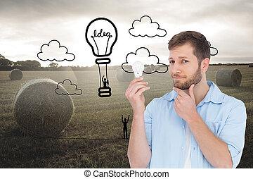 Una imagen compuesta de modelo guapo sosteniendo una bombilla