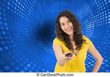 Una imagen compuesta de sonriente mujer de pelo rizado y bonita cambiando de canal con control remoto