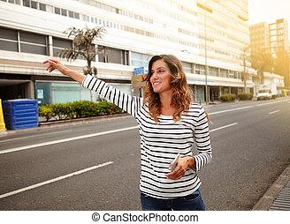 Una joven alegre llamando a un taxi en la calle City