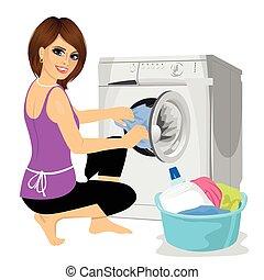 Una joven ama de casa poniendo un trapo en la lavadora