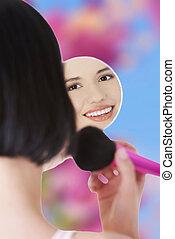 Una joven aplicando maquillaje